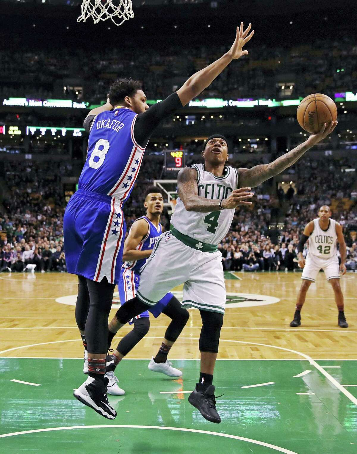 Boston Celtics guard Isaiah Thomas (4) is covered by Philadelphia 76ers center Jahlil Okafor (8) on a drive to the basket during the first quarter in Boston Wednesday.