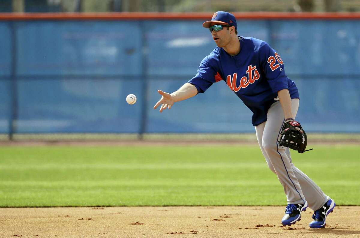 New York Mets second baseman Neil Walker tosses the ball to second base during a spring training baseball workout Wednesday in Port St. Lucie, Fla.