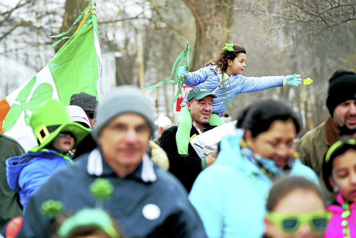 A girl throws candy to the crowd on River Street during the Milford St. Patrick's Day Parade Saturday afternoon March 18, 2017. See Photo Gallery of the St. Patrick's Day at photos.newhavenregister.com