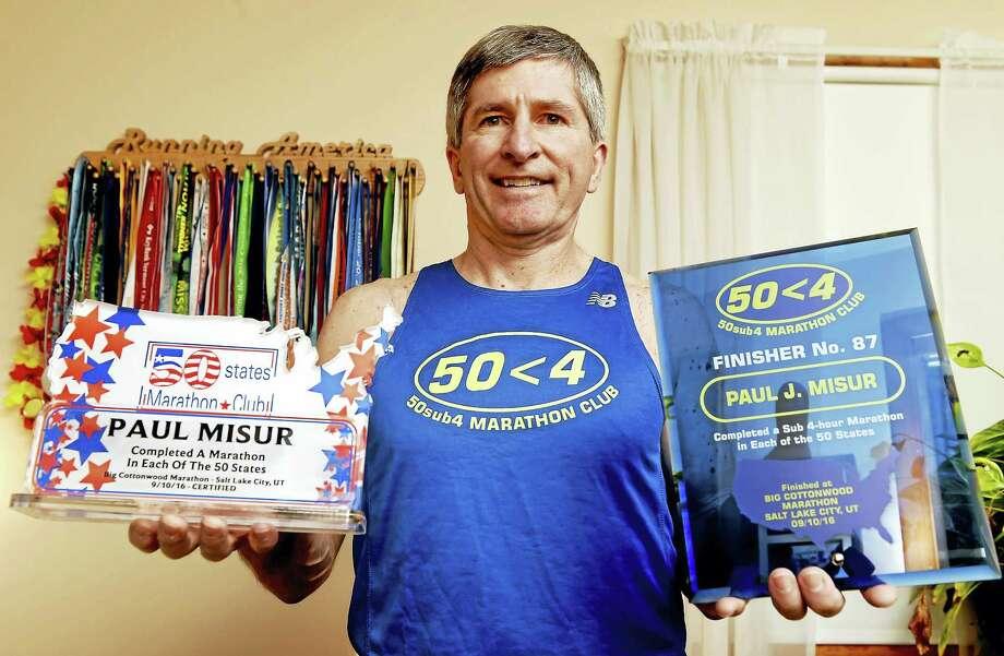 Paul Misur of Shelton, who has run marathons in all 50 states, at his home. Photo: Peter Hvizdak — New Haven Register   / ©2017 Peter Hvizdak