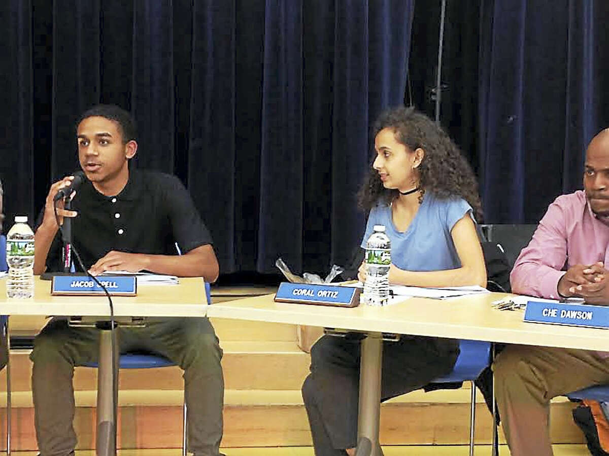 Jacob Spell, a student member of the New Haven Board of Education, addresses issues facing the student body of Cortlandt V.R. Creed Health and Sports Sciences High School, where he is a student. Beside him are student board member Coral Ortiz and board member Che Dawson.