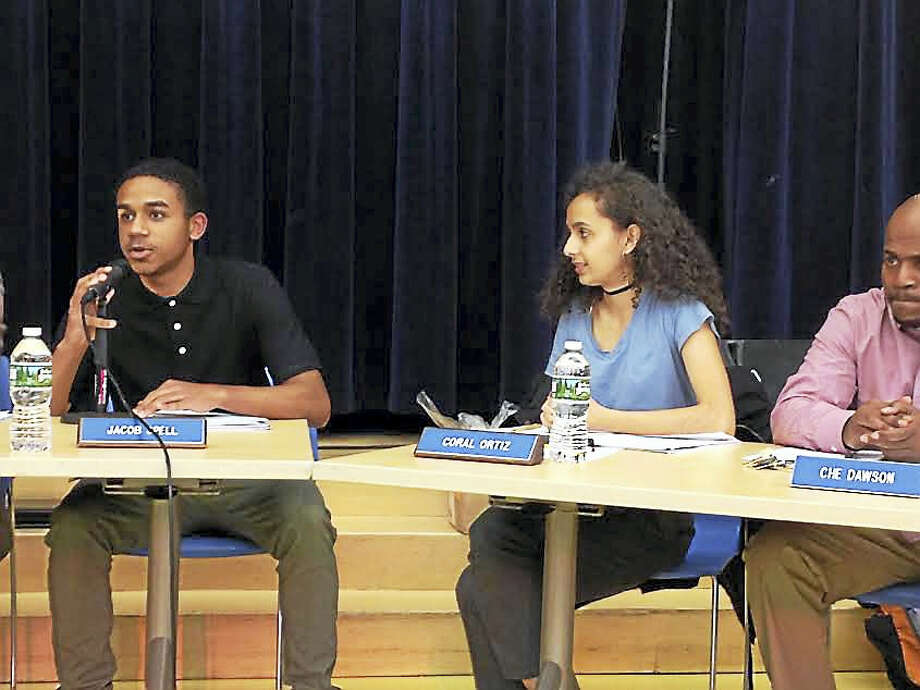 Jacob Spell, a student member of the New Haven Board of Education, addresses issues facing the student body of Cortlandt V.R. Creed Health and Sports Sciences High School, where he is a student. Beside him are student board member Coral Ortiz and board member Che Dawson. Photo: Brian Zahn — New Haven Register