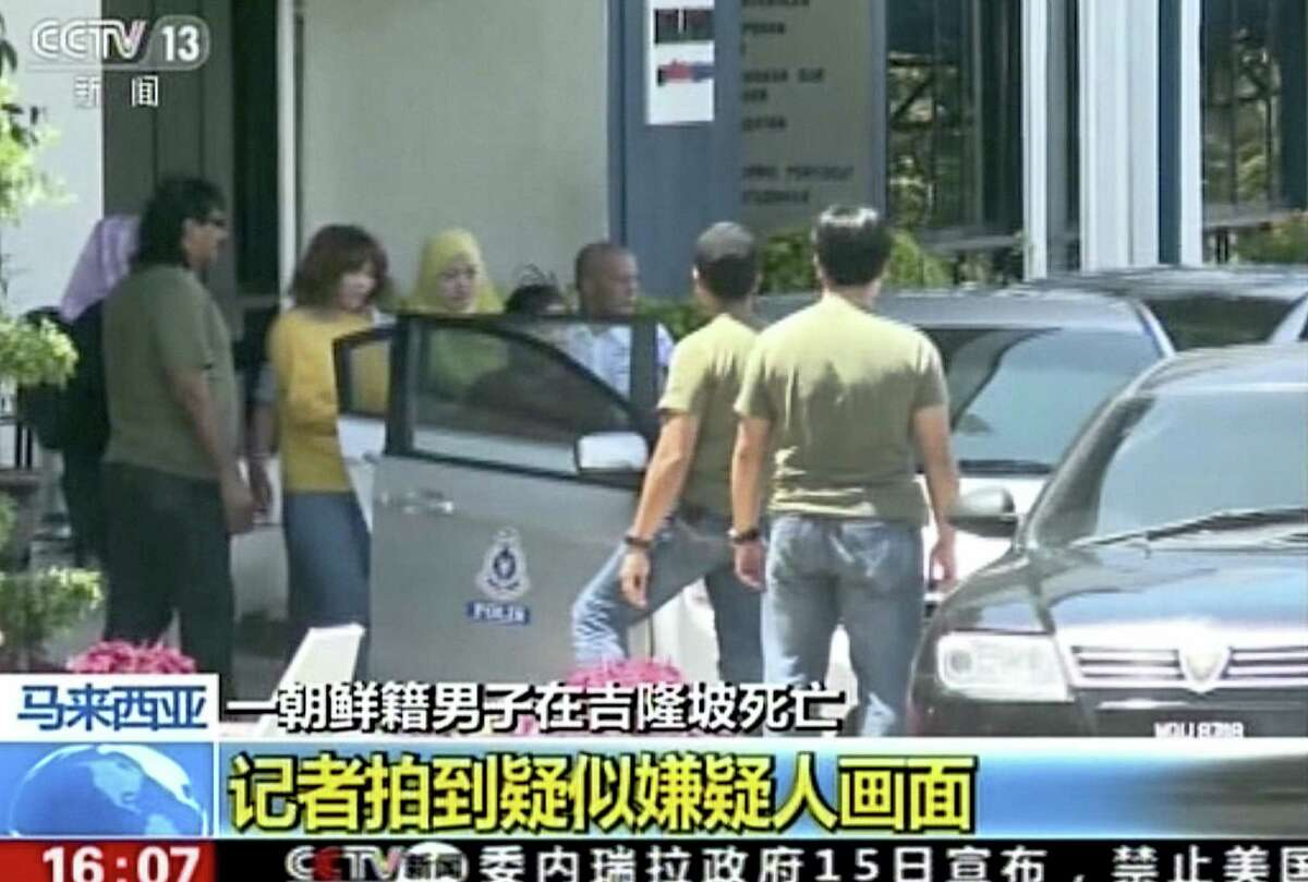In this image from video released on Thursday, Feb. 16, 2017 by China's CCTV and made available via AP Video, a woman wearing a yellow, third from left, suspected of involvement in the apparent assassination of Kim Jong Nam, the half brother of North Korean leader Kim Jong Un, is escorted by Malaysian officials to a vehicle in Kuala Lumpur, Malaysia.
