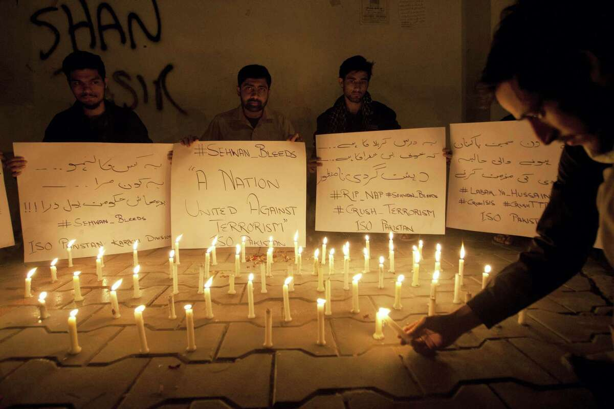 Pakistani students light candles to condemn the recent attack on a shrine in interior Sind province, Thursday, Feb. 16, 2017, in Karachi, Pakistan. An Islamic State suicide bomber targeted worshippers at a famous shrine in southern Pakistan on Thursday, killing dozens of worshippers and left hundreds of people wounded, officials said.