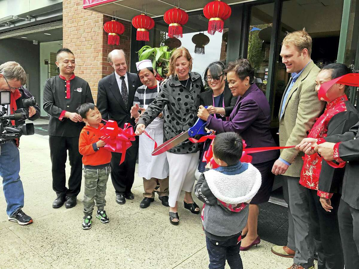 Mayor Toni Harp, third from right, joins Hunan House owners, chefs and other city and local officials in a ribbon-cutting for the new authentic Chinese restaurant Monday in New Haven.