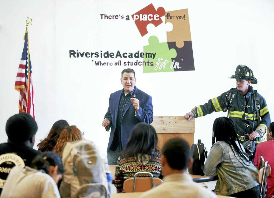 IAFF Local 825 President Frank Ricci, center, speaks to students at Riverside Academy in New Haven Tuesday about their upcoming visit to the National September 11 Memorial & Museum in New York City. At right is New Haven Firefighter Mike Milano. Photo: Arnold Gold — New Haven Register