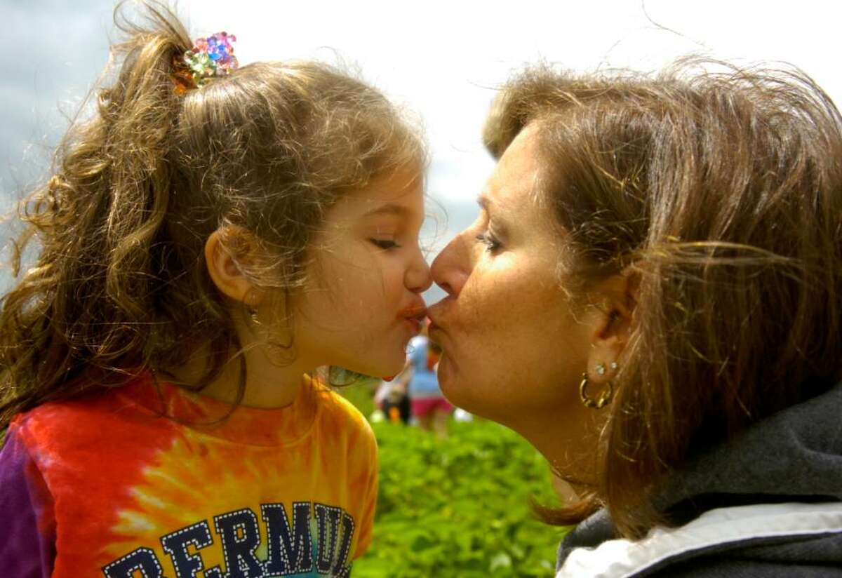 Ella Celozzi, 3, of Naugatuck, gives her grandmother Pam Parisi of Ansonia a kiss covered in strawberry juice at Jones Family Farms in Shelton on Friday, June 11, 2010.