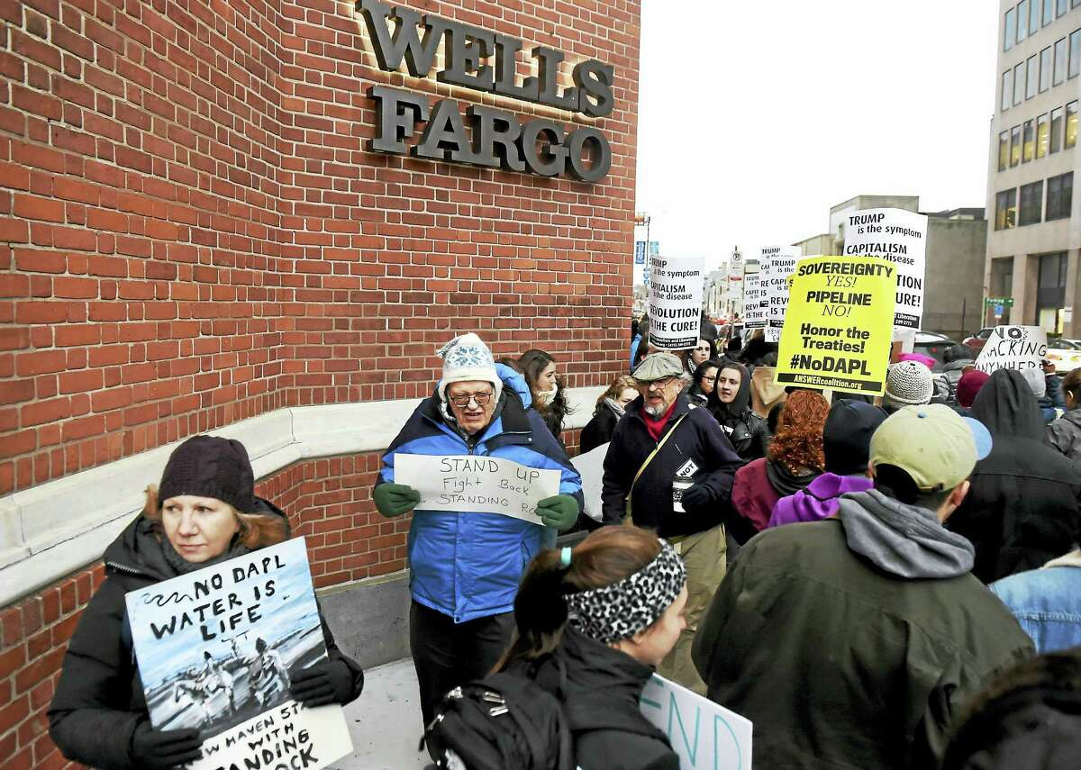 Protesters demonstrate in front of the Wells Fargo bank branch on the corner of College and Elm Streets in New Haven Friday against the Dakota Access Pipeline project.