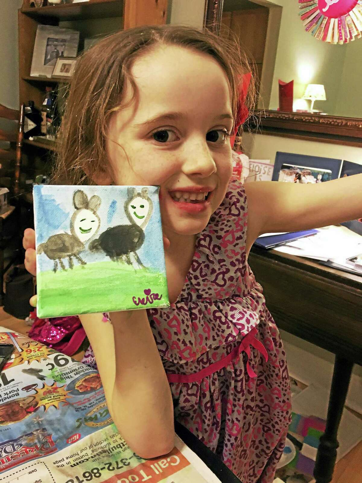 Eloise Mackell shows off one of the drawings she sold to help the Milford Animal Shelter.