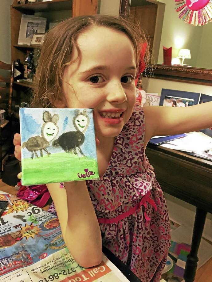 Eloise Mackell shows off one of the drawings she sold to help the Milford Animal Shelter. Photo: CONTRIBUTED PHOTO — Glenn L. Laudenslager IV