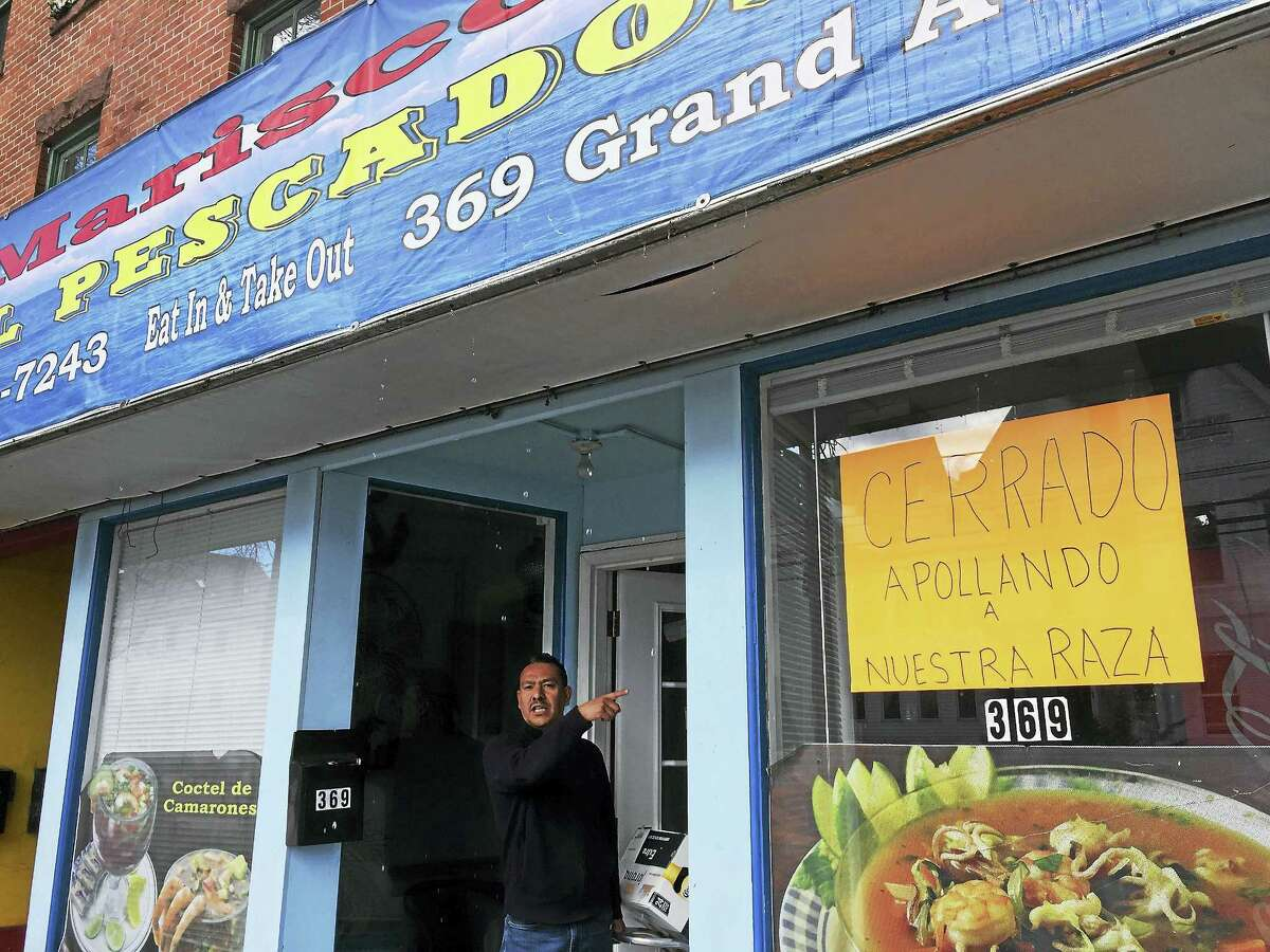 Moises Vargas gestures toward other businesses on Grand Avenue outside his seafood restuarant, Mariscos El Pescador, which he closed for the day in solidarity with Day Without Immigrants.