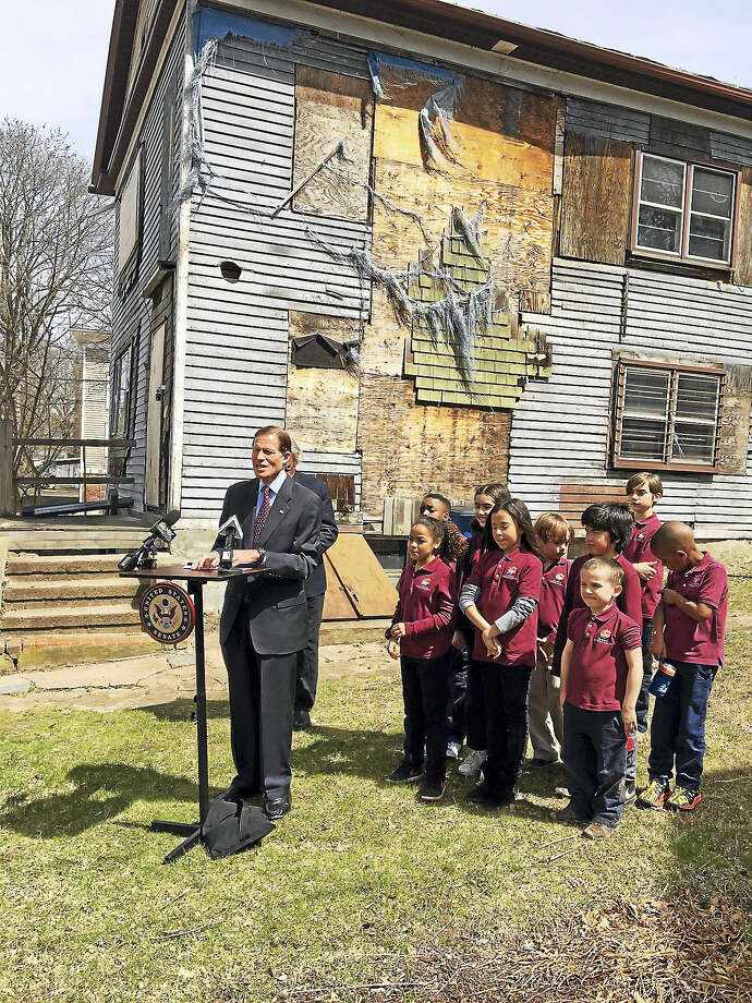 Students from All Nations Christian Academy listen to U.S. Sen. Richard Blumenthal speak about rehabbing the Ghost House, behind him. Photo: Mary E. O'Leary — New Haven Register