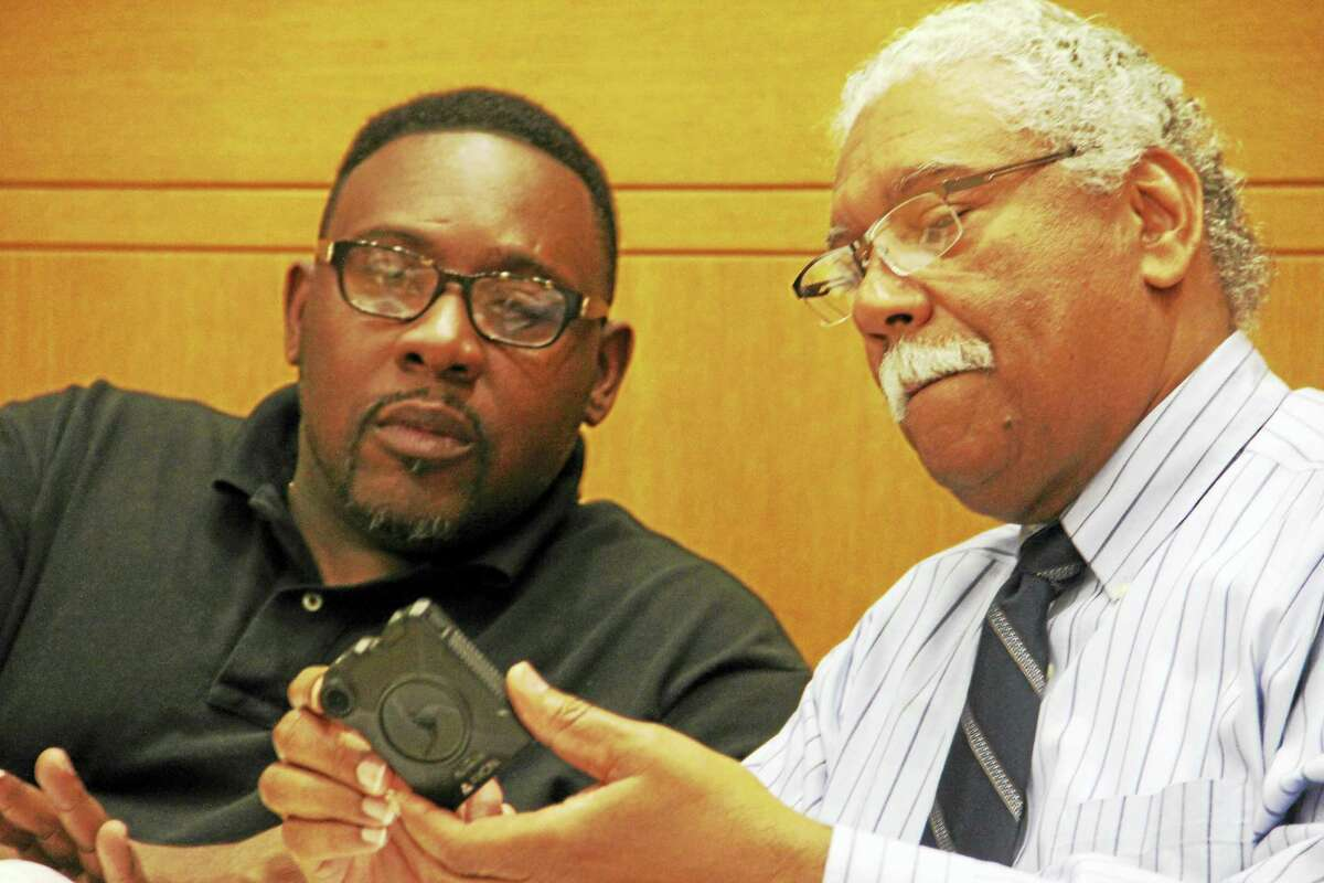 From left, New Haven Alders Brian Wingate, D-29, and Gerald Antunes, D-12, examine a Taser Axon body camera during a Public Safety Committee public hearing Tuesday at City Hall.