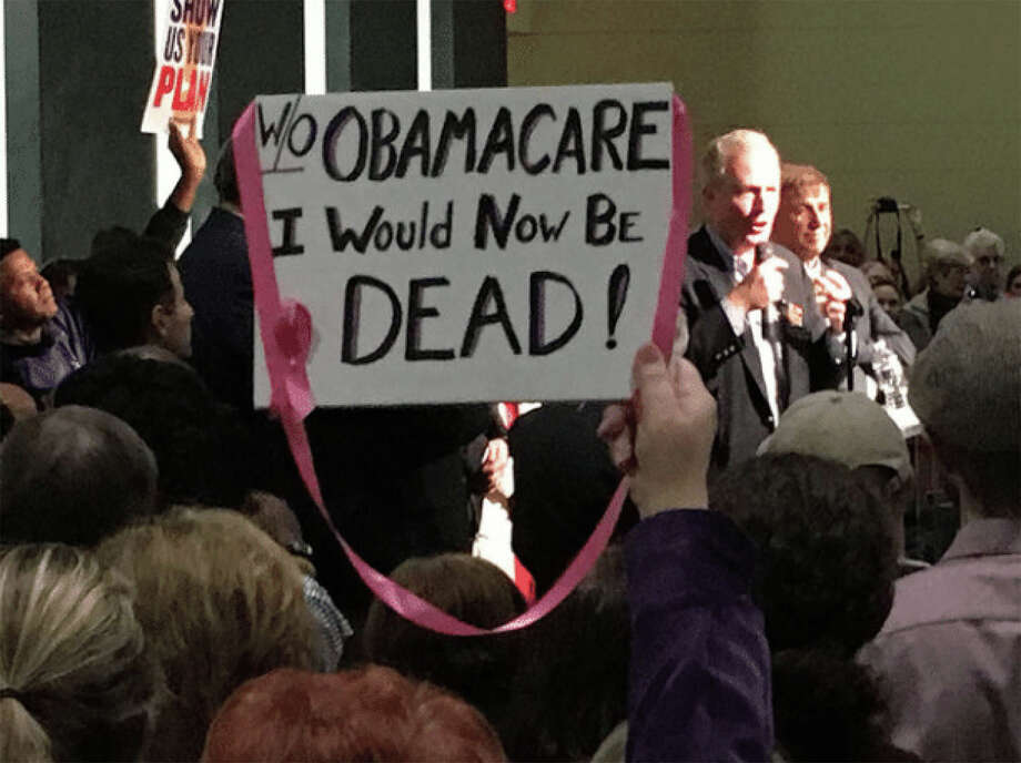 A supporter of the Affordable Care Act hoists a sign for Sen. Chris Van Hollen, D-Md., to see at a rally in Bowie, Md., on Sunday. Photo: Washington Post Photo By David Weigel  / The Washington Post