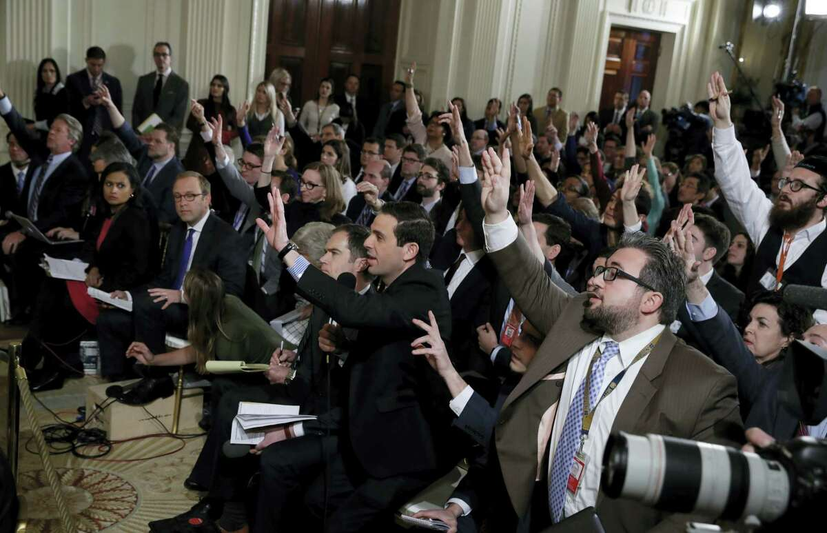 Reporters raise their hands during President Donald Trump news conference on Thursday in the East Room of the White House in Washington.