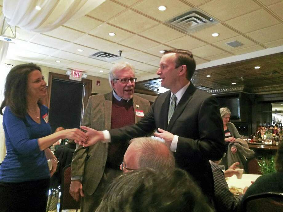 US Senator Chris Murphy, D-Conn., shakes the hand of anunidentified female constituent Friday in Cheshire. Sheldon Dill,president of the Cheshire Chamber of Commerce is shown at center. Photo: Digital First Media