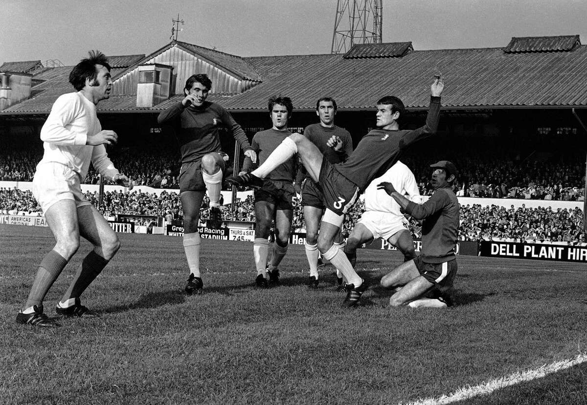 In this Oct. 18, 1969 photo, Chelsea's Eddie McCreadie, second right, kicks clear from scrimmage in front West Bromwich's Jeff Astle, left, during the English League Division one soccer match between Chelsea and West Bromwich Albion at Stamford Bridge Stadium in London. The degenerative damage potentially caused by repeated blows to the head in soccer has been highlighted by a rare study of brains of a small number of retired players who developed dementia, released on Feb. 15, 2017. Concerns have grown in Britain about the impact of head injuries after campaigning by the family of former England striker Jeff Astle, whose death at age 59 in 2002 was attributed to repeatedly heading heavy, leather balls.
