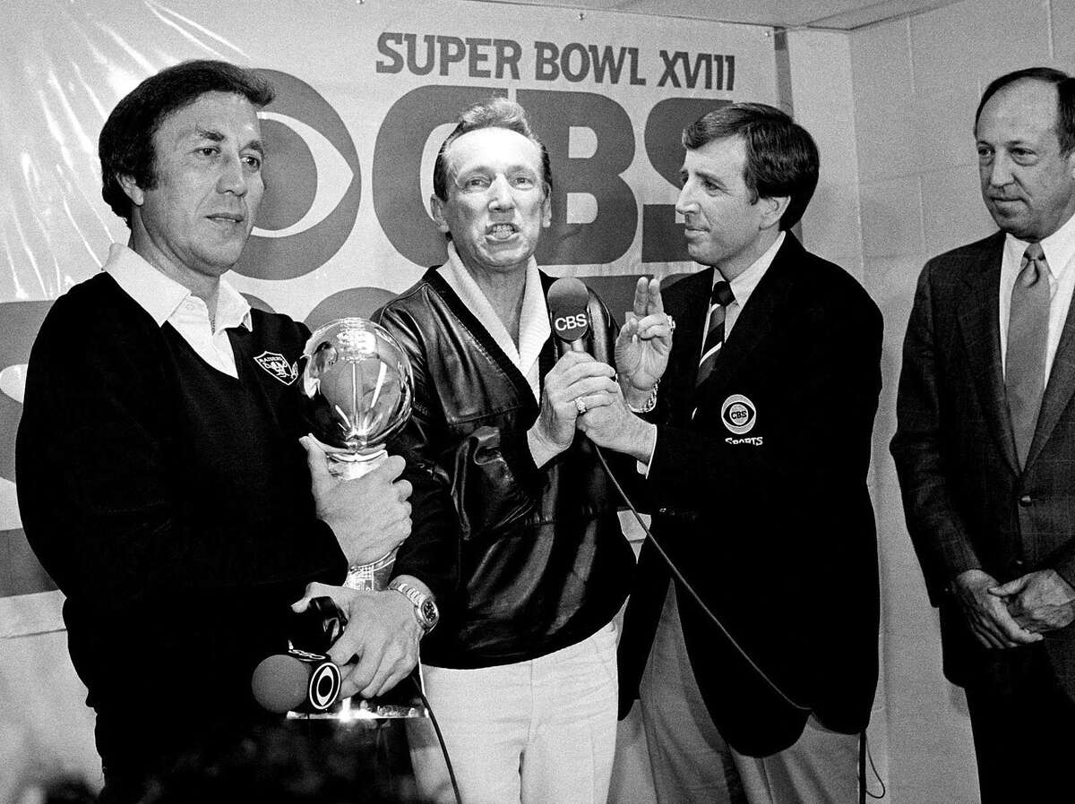 Oakland Raiders coach Tom Flores clutches the Super Bowl trophy as Raiders managing general partner Al Davis is interviewed by Brent Musburger in the locker room after their 38-9 win over the Washington Redskins in Super Bowl XVIII in Tampa, Fla. in 1984.