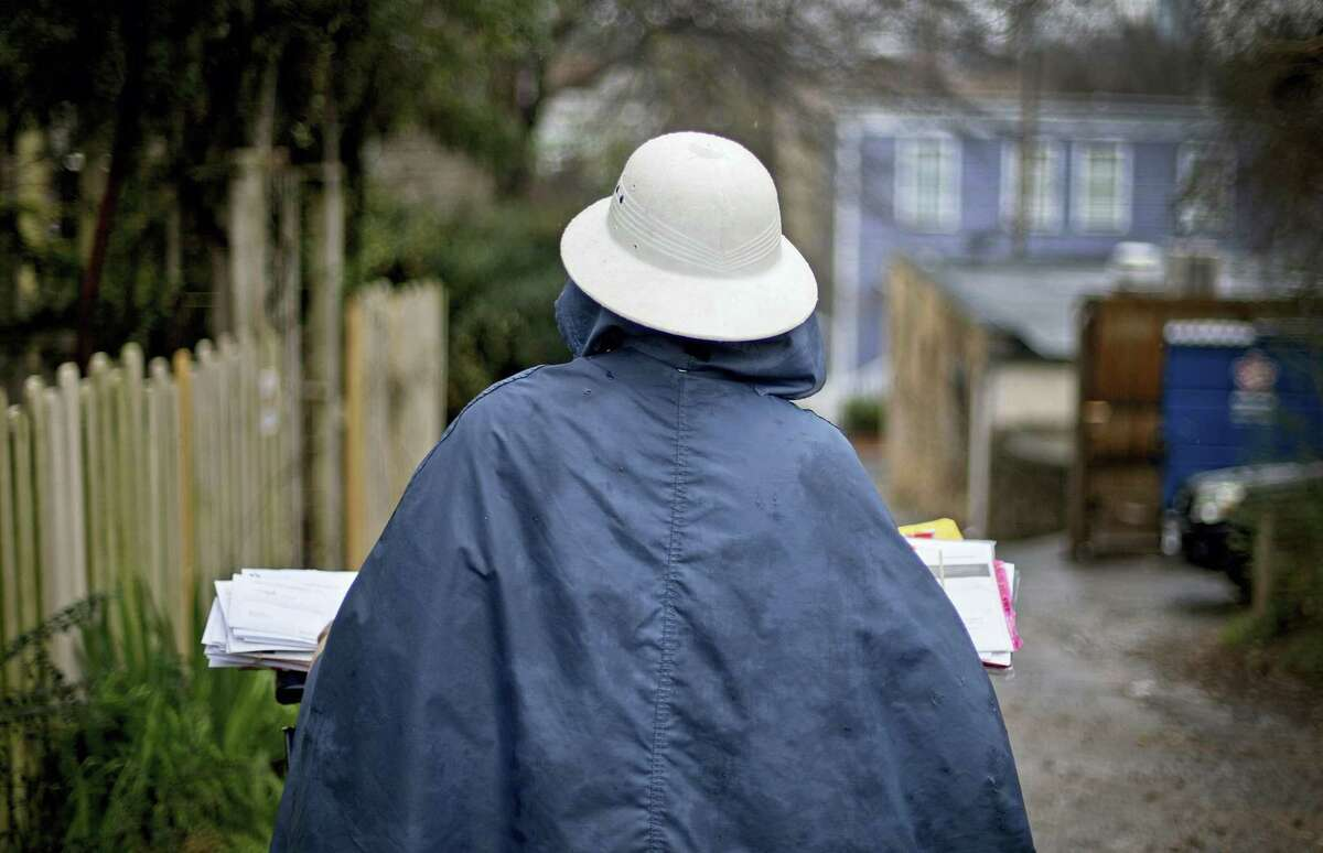 A U.S. Postal Service letter carrier delivers mail in the rain in Atlanta.