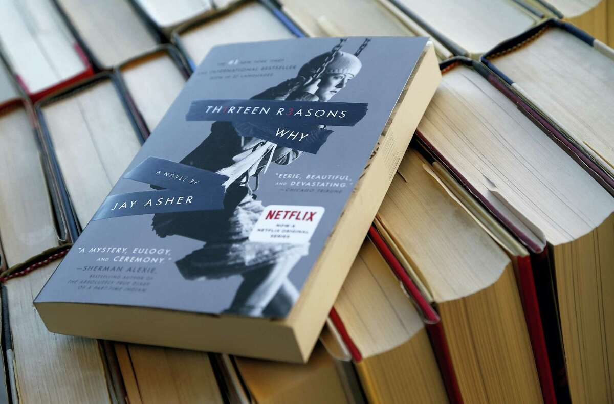 "This photo shows the book ""Thirteen Reasons Why"" in a photo illustration, May 15, 2017, in Phoenix. As a Colorado community mourns the loss of seven students who killed themselves, a top school district official ordered librarians to temporarily stop circulating a book that's the basis for Netflix's popular new series ""13 Reasons Why,"" which some critics say romanticizes suicide."