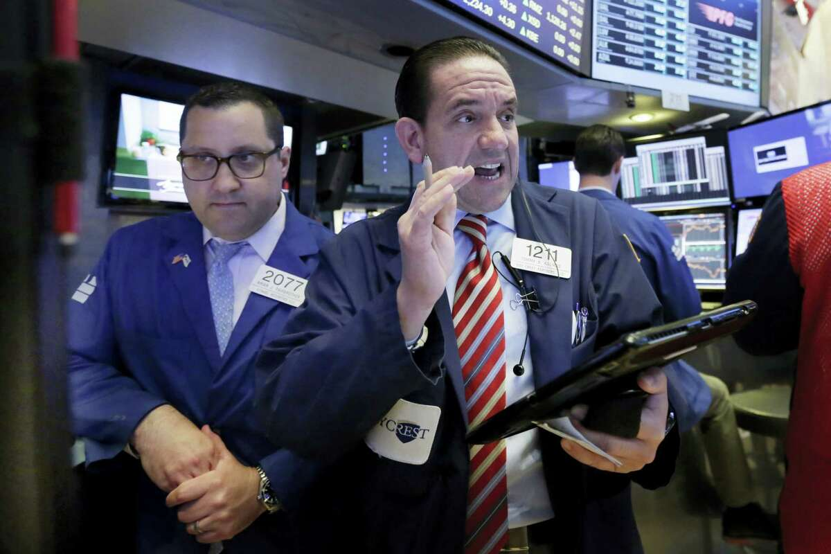 Specialist Brian Fairbrother, left, and trader Tommy Kalikas work on the floor of the New York Stock Exchange Tuesday.