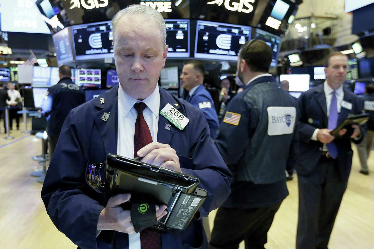 Trader James Riley, left, works on the floor of the New York Stock Exchange Tuesday.
