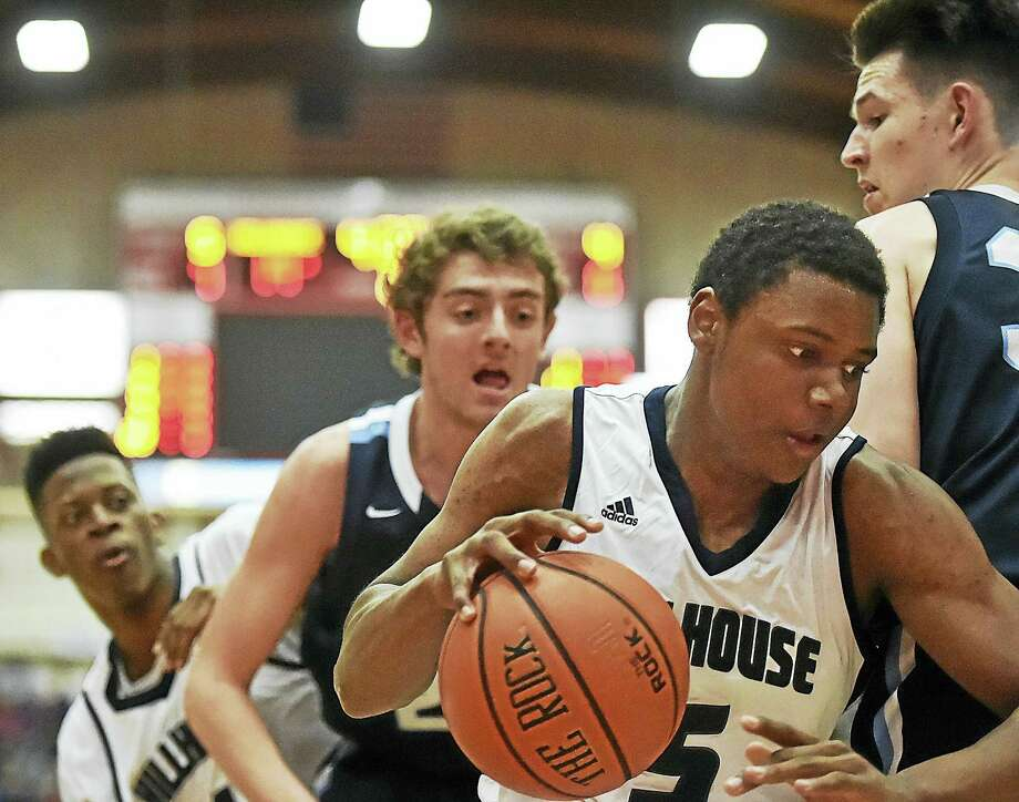 Hillhouse junior Christian Adams drives the paint as East Catholic junior Matthew Veretto defends in the Academics 53-45 win Wednesday night in the CIAC class LL semifinal game at the Chase Family Arena at the University of Hartford in West Hartford. Photo: Catherine Avalone — New Haven Register   / Catherine Avalone/New Haven Register