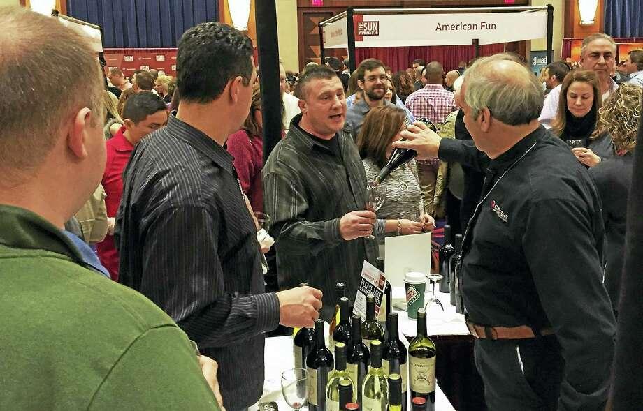 A Connecticut Distributors representative pours a sample at last year's Wine Fest. Photo: Joe Amarante — Register