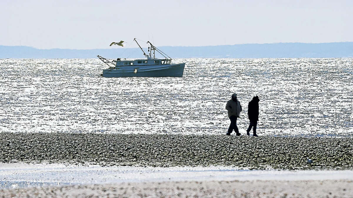 (Arnold Gold-New Haven Register) A couple walk along a sandbar at Silver Sand State Park in Milford on 3/19/2017.