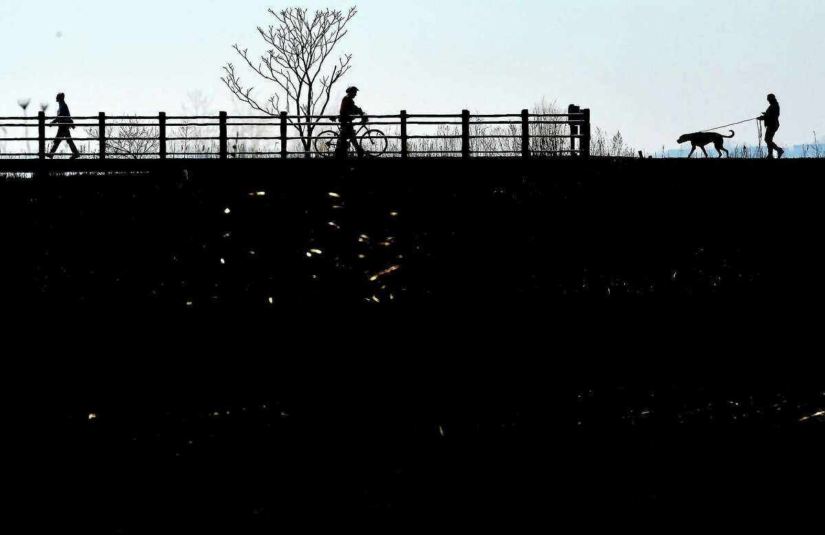 (Peter Hvizdak - New Haven Register) A harbinger of spring, people take the opportunity of a warm winter day to stroll, bike or walk a dog on a Silver Sands State Park boardwalk in Milford Wednesday afternoon, March 9, 2016.