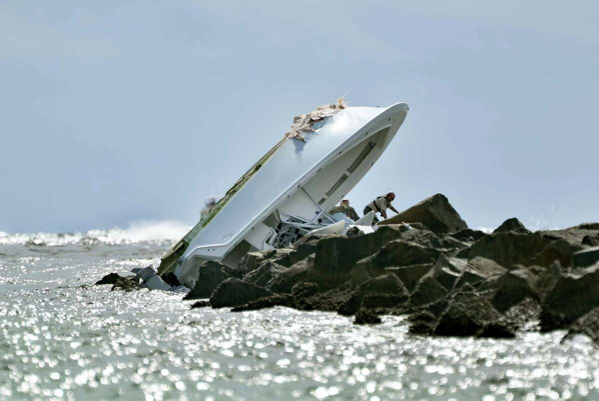 Investigators inspect an overturned boat as it rests on a jetty after a crash on Sept. 25, 2016, off Miami Beach, Fla.