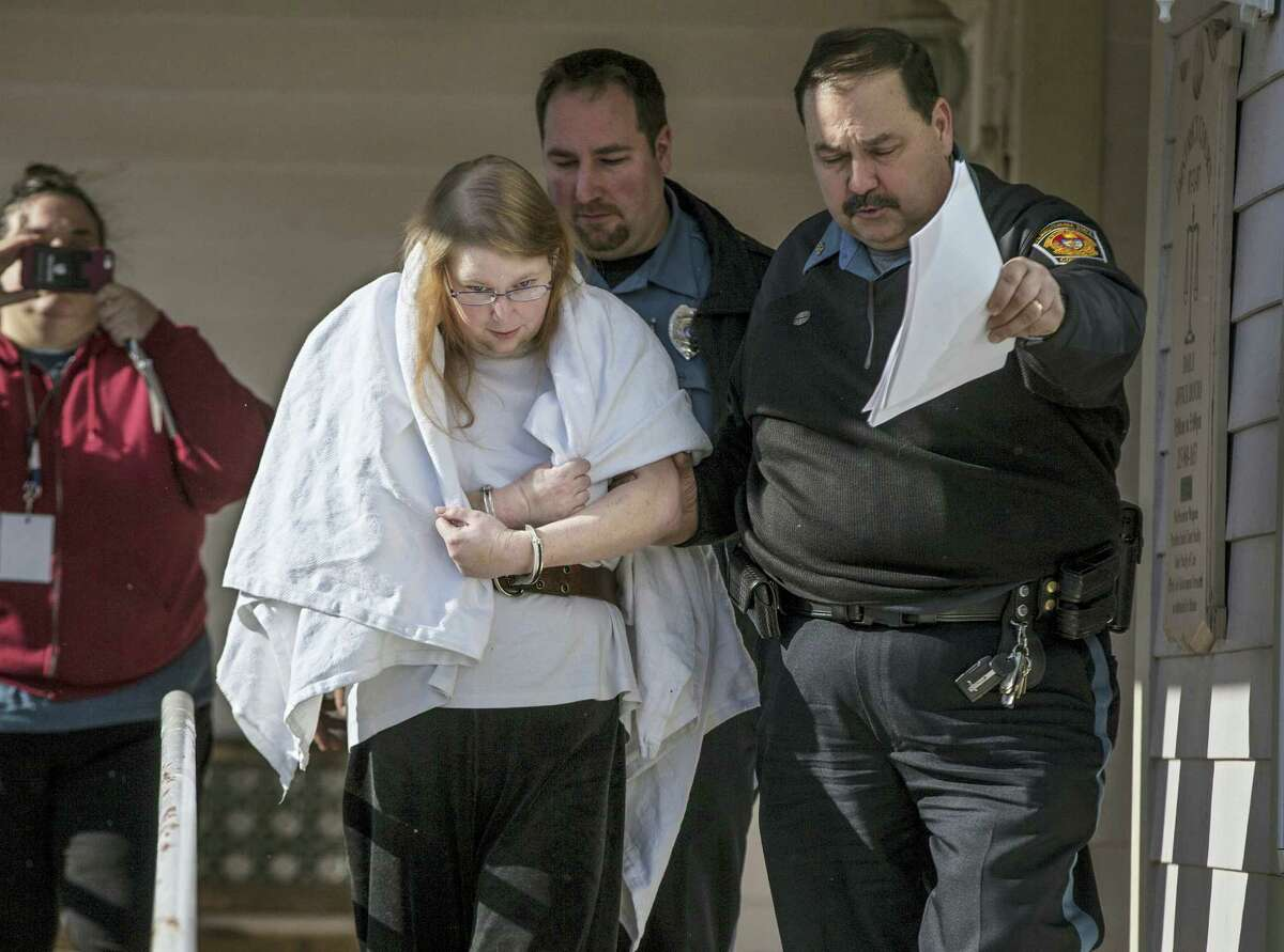 """In this Jan. 8, 2017, file photo, Sara Packer, center, handcuffed, the adoptive mother of Grace Packer, is led out of District Court in Newtown, Pa., by Pennsylvania Constables and taken into custody. Packer, whose teenage daughter's dismembered remains were found in the woods last fall, has been charged along with her boyfriend Jacob Sullivan with killing the girl in a """"rape-murder fantasy"""" the couple shared, a prosecutor said."""