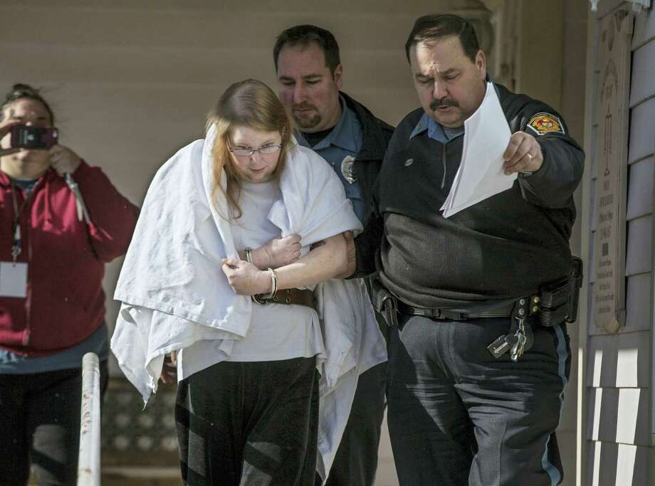 """In this Jan. 8, 2017, file photo, Sara Packer, center, handcuffed, the adoptive mother of Grace Packer, is led out of District Court in Newtown, Pa.,  by Pennsylvania Constables and taken into custody. Packer, whose teenage daughter's dismembered remains were found in the woods last fall, has been charged along with her boyfriend Jacob Sullivan with killing the girl in a """"rape-murder fantasy"""" the couple shared, a prosecutor said. Photo: Michael Bryant/The Philadelphia Inquirer Via AP, File    / The Philadelphia Inquirer"""