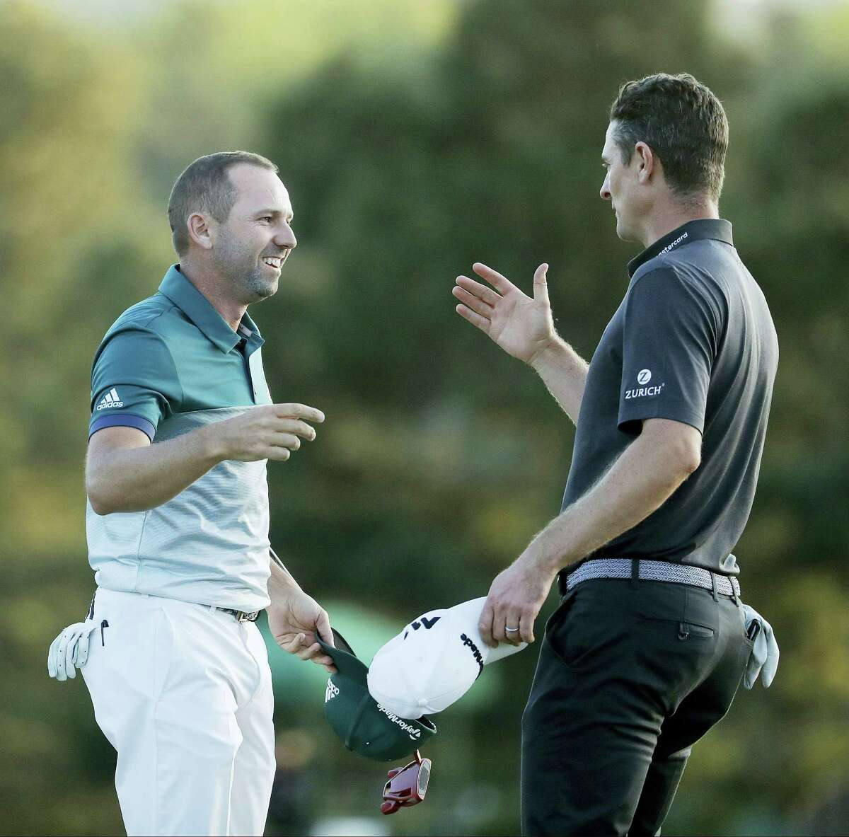 Sergio Garcia, of Spain, talks to Justin Rose, of England, after making his birdie putt on the 18th green to win the Masters golf tournament after a playoff Sunday in Augusta, Ga.