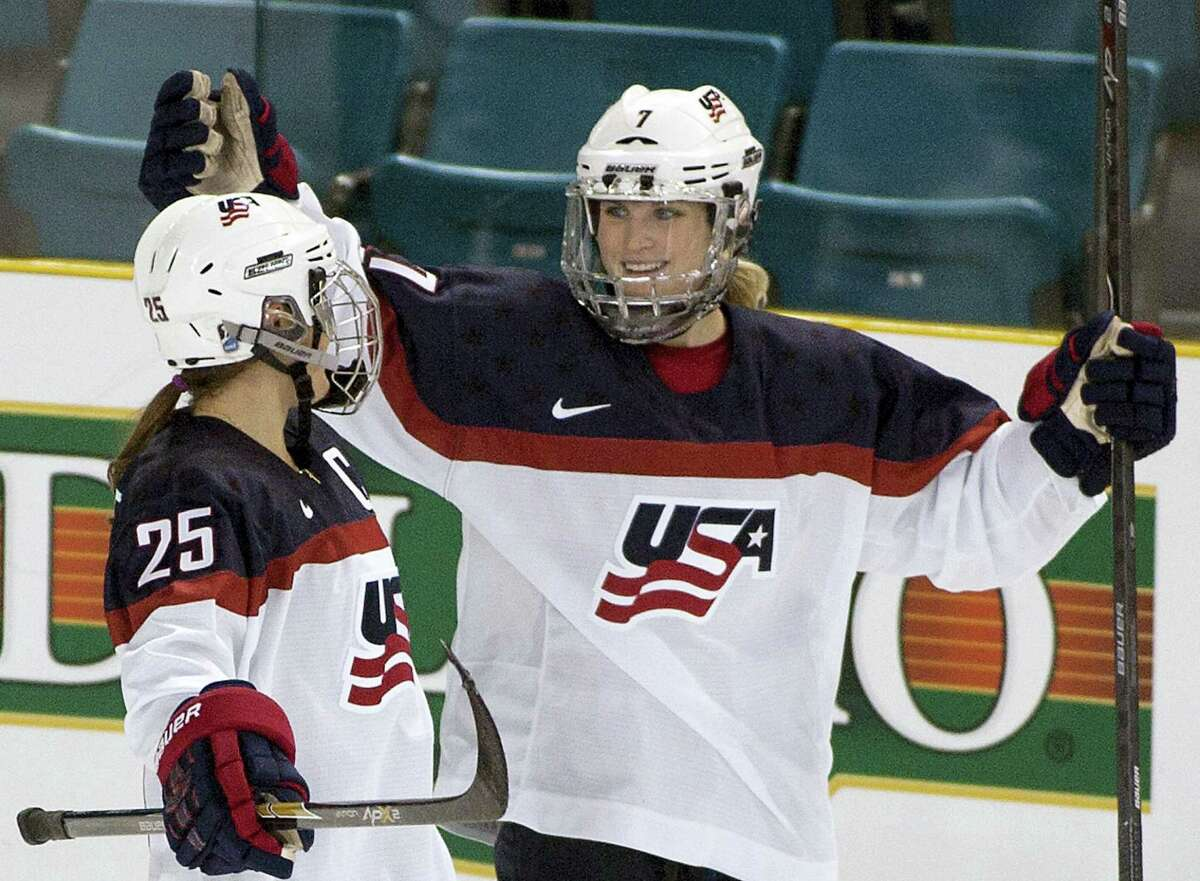 In this Nov. 4, 2014 photo, Team United States' Monique Lamoureux, right, celebrates her goal against Team Finland with teammate Alex Carpenter during the third period at the Four Nations Cup women's hockey tournament in Kamloops, British Columbia. The U.S. women's hockey team is threatening to boycott the world championships because of a wage dispute. The team announced Wednesday that they will not participate in the International Ice Hockey Federation tournament that begins March 31, 2017 in Plymouth, Michigan.