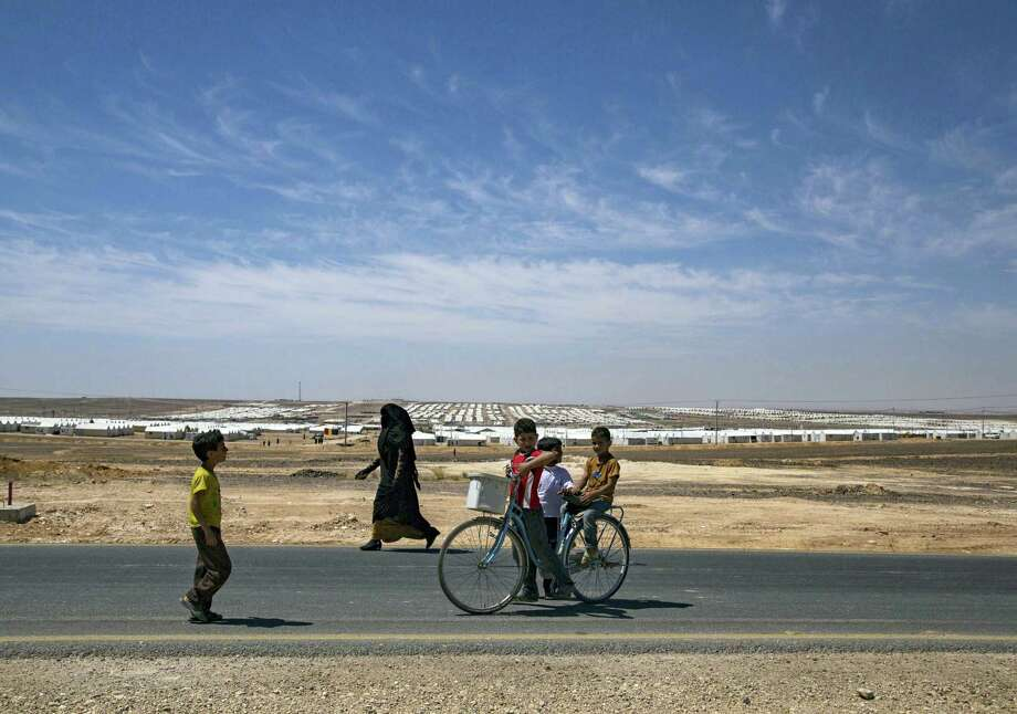 Syrian refugees walk near the Azraq Refugee Camp where the U.N. refugee agency inaugurated a solar power plant, in Jordan'Äôs northern desert, May 17, 2017. The agency said the plant, funded by a foundation of the global home furnishings company Ikea, makes Azraq the world's first refugee camp powered by renewable energy and saves $1.5 million a year in electricity costs.   Elena Boffetta — AP Photo Photo: AP / AP