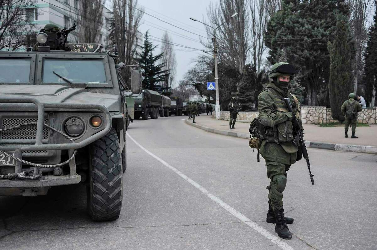 Troops in unmarked uniforms stand guard in Balaklava on the outskirts of Sevastopol, Ukraine, Saturday, March 1, 2014. An emblem on one of the vehicles and their number plates identify them as belonging to the Russian military. Ukrainian officials have accused Russia of sending new troops into Crimea, a strategic Russia-speaking region that hosts a major Russian navy base. The Kremlin hasn't responded to the accusations, but Russian lawmakers urged President Putin to act to protect Russians in Crimea.