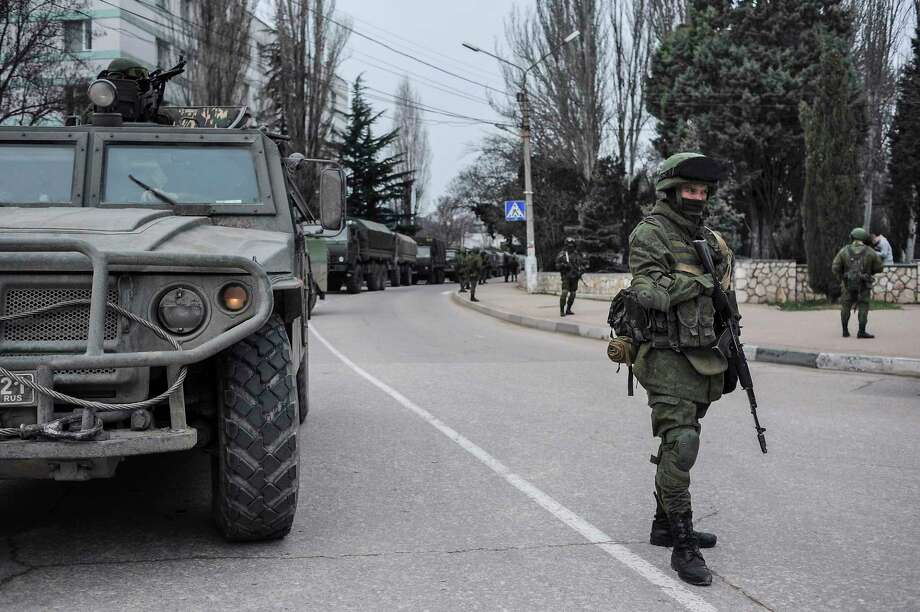 Troops in unmarked uniforms stand guard in Balaklava on the outskirts of Sevastopol, Ukraine, Saturday, March 1, 2014. An emblem on one of the vehicles and their number plates identify them as belonging to the Russian military. Ukrainian officials have accused Russia of sending new troops into Crimea, a strategic Russia-speaking region that hosts a major Russian navy base. The Kremlin hasn't responded to the accusations, but Russian lawmakers urged President Putin to act to protect Russians in Crimea. Photo: Andrew Lubimov — AP Photo / AP