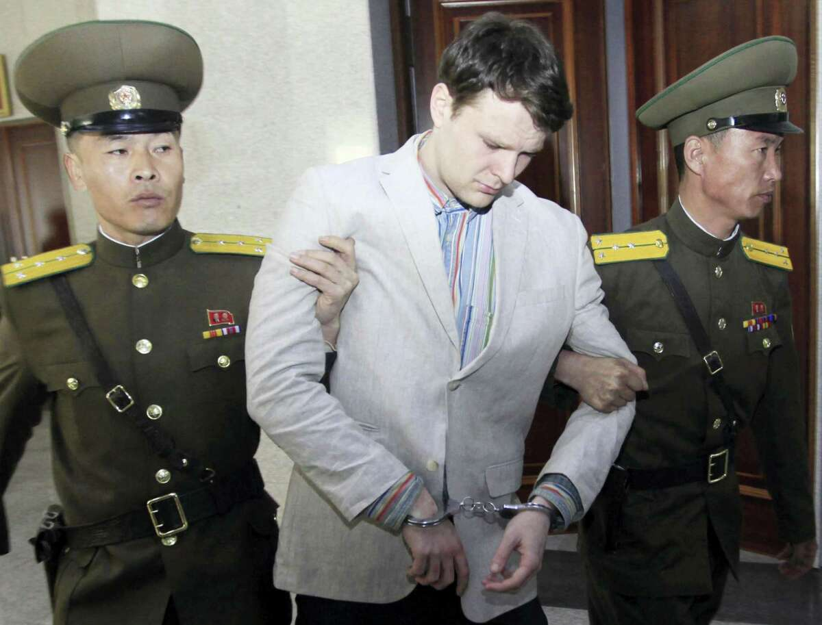 Jon Chol Jin/THE ASSOciated press American student Otto Warmbier, center, is escorted at the Supreme Court in Pyongyang, North Korea.