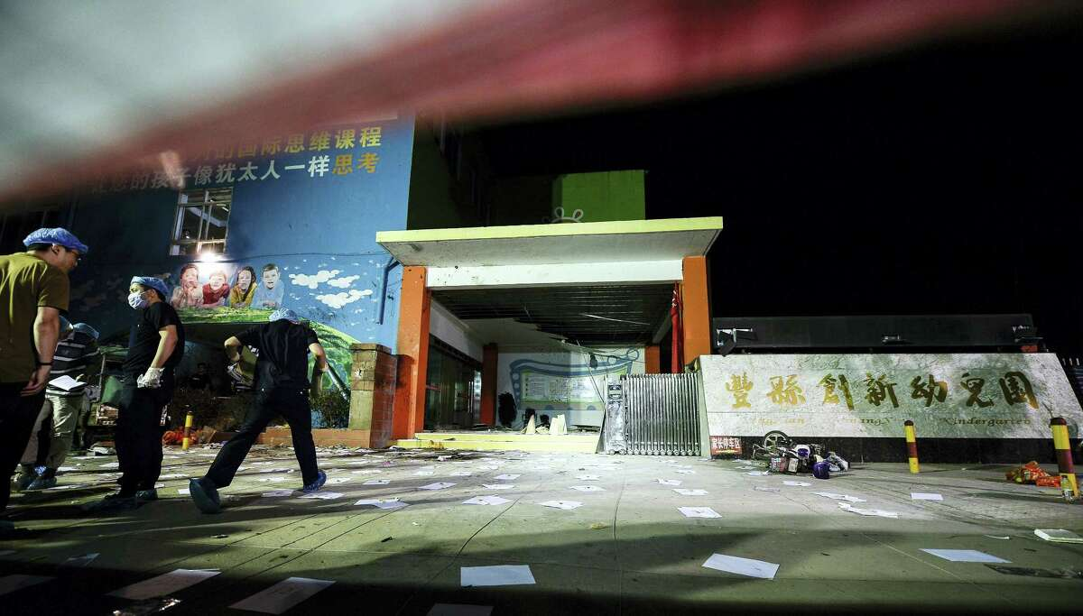 In this photo released by China's Xinhua News Agency, investigators work early Friday, June 16, 2017, at the scene of an explosion outside a kindergarten in Fengxian County in eastern China's Jiangsu Province. Several people were killed and dozens more injured in an explosion Thursday at the front gate of the kindergarten in eastern China as relatives were picking up their children at the end of the school day, local officials said.