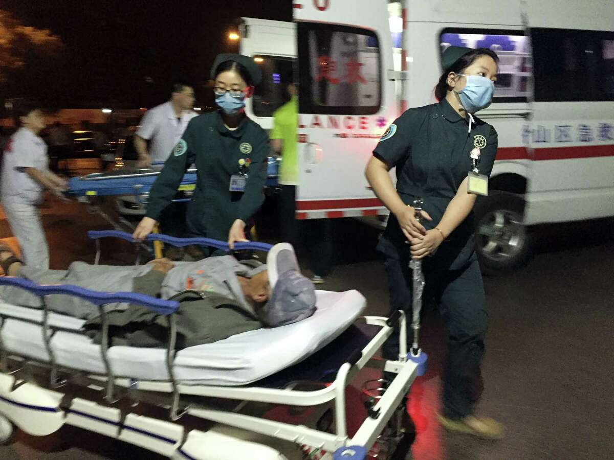 In this photo released by China's Xinhua News Agency, medical workers transport a person injured in an explosion outside a kindergarten into a hospital in Fengxian County in eastern China's Jiangsu Province early Friday, June 16, 2017. Several people were killed and dozens more injured in an explosion Thursday at the front gate of the kindergarten in eastern China as relatives were picking up their children at the end of the school day, local officials said.