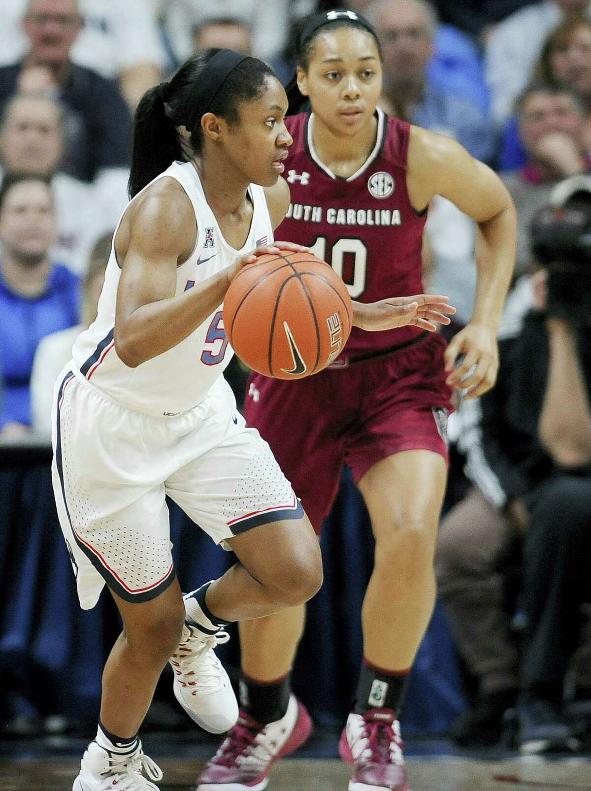 UConn's Crystal Dangerfield dribbles as South Carolina's Allisha Gray, right, defends, in the second half of the Huskies' 100th straight victory