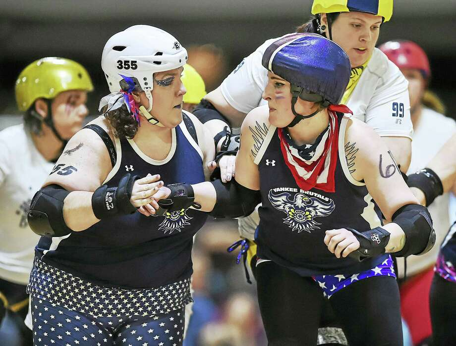 Smacadameunut Cooke, number 355, and Jackie Kero-Whack, number 615 of the Yankee Brutals attempt to block Damn Yell, number 99 of the Battle Cats on a flat track at Insports in Trumbull. Photo: Catherine Avalone — New Haven Register   / Catherine Avalone/New Haven Register