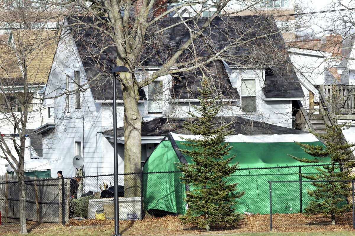"""A large green tent is seen in the back of a house on Hayward Street in Manchester, N.H., where authorities searched for clues in the missing person's case of Denise Beaudin. State authorities said the case is connected to one involving four bodies found in two steel drums between 1985 and 2000 in a state park. Beaudin's family last saw her on Thanksgiving 1981, when she was 23, with her boyfriend, Robert """"Bob"""" Evans, and her infant daughter."""