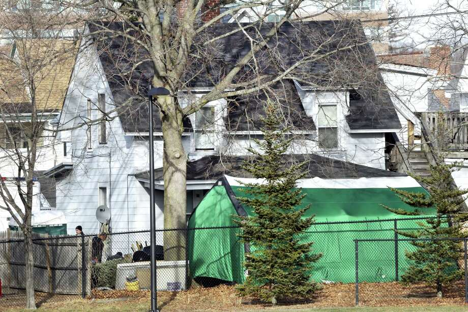"""A large green tent is seen in the back of a house on Hayward Street in Manchester, N.H., where authorities searched for clues in the missing person's case of Denise Beaudin. State authorities said the case is connected to one involving four bodies found in two steel drums between 1985 and 2000 in a state park. Beaudin's family last saw her on Thanksgiving 1981, when she was 23, with her boyfriend, Robert """"Bob"""" Evans, and her infant daughter. Photo: Elise Amendola — AP File Photo / Copyright 2017 The Associated Press. All rights reserved."""