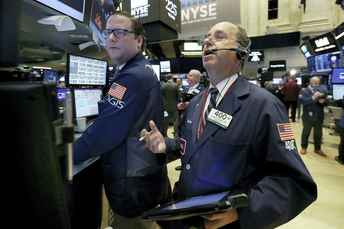 Specialist Gregg Maloney, left, and trader Gordon Charlop work on the floor of the New York Stock Exchange Thursday.