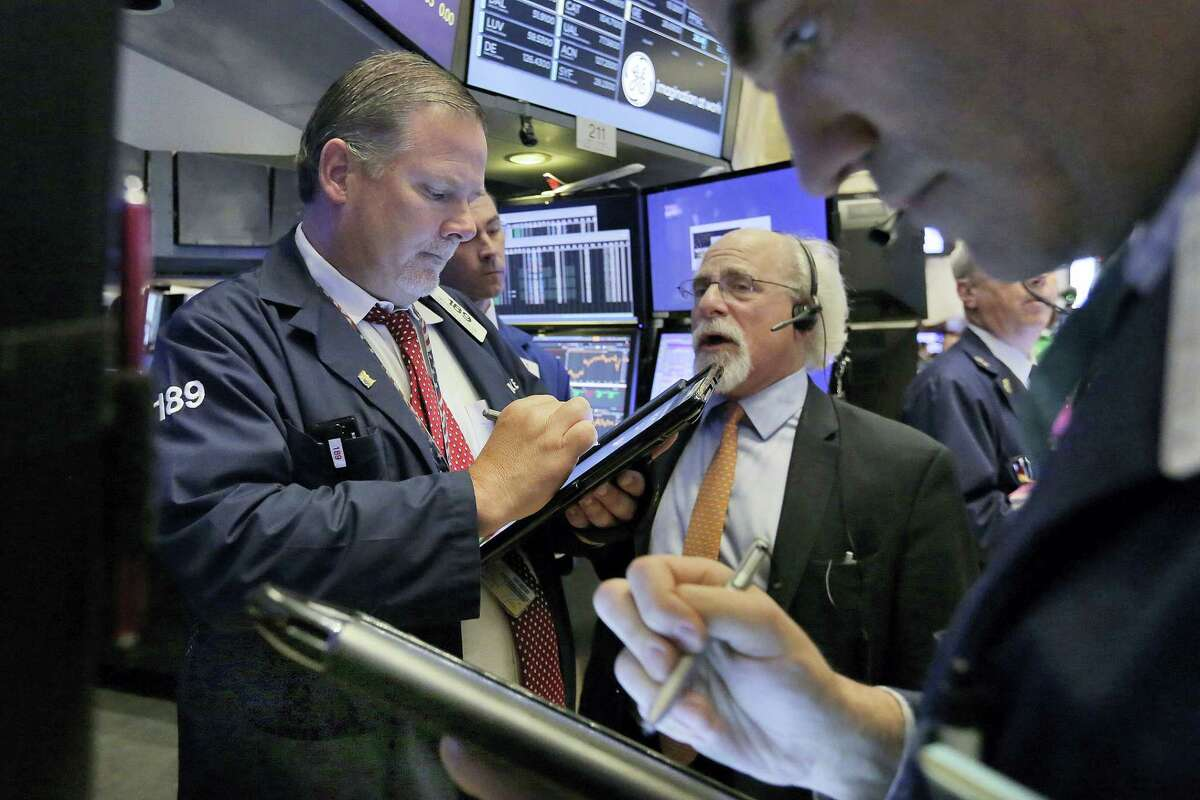 From left, traders Michael Conlon, Peter Tuchman and Gregory Rowe work on the floor of the New York Stock Exchange Thursday.