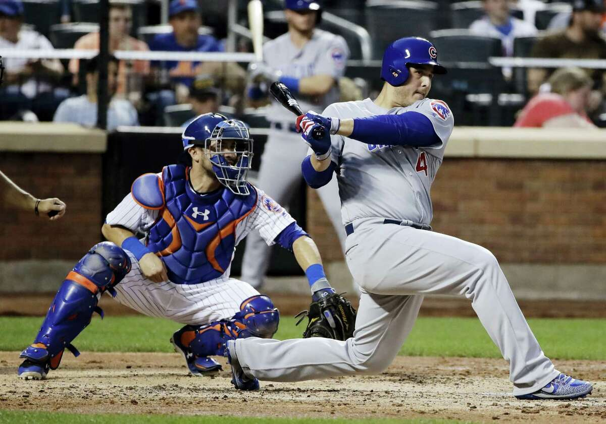 Chicago Cubs' Anthony Rizzo (44) follows through on an hits an RBI double as New York Mets catcher Travis d'Arnaud watches during the third inning of a baseball game on Tuesday.