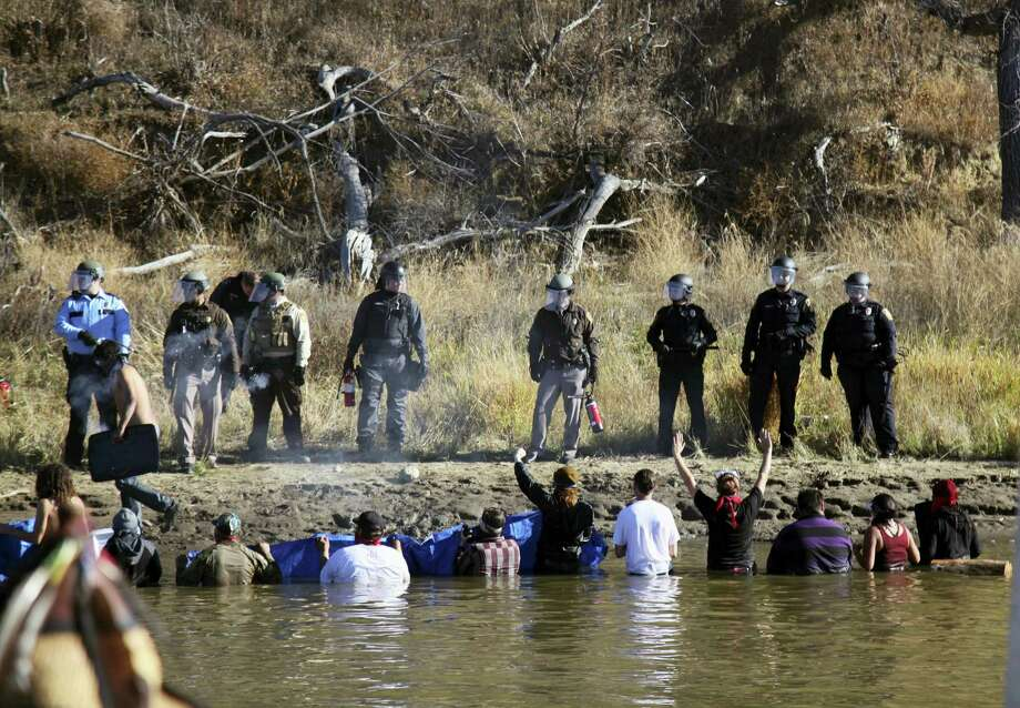 In this Nov. 2, 2016, file photo, protesters demonstrating against the expansion of the Dakota Access pipeline wade in cold creek waters confronting local police near Cannon Ball, N.D. North Dakota officials appear poised to go after the U.S. government  — and thus U.S. taxpayers — to recoup more than $38 million in state expenses related to months of protests against the Dakota Access pipeline. Photo: AP Photo/John L. Mone, File    / Copyright 2017 The Associated Press. All rights reserved.