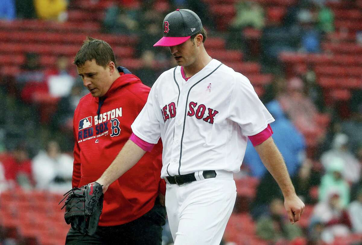 Drew Pomeranz, right, leaves the field with a trainer during the fourth inning Sunday.